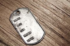 Military token closeup. On wooden background Royalty Free Stock Photos