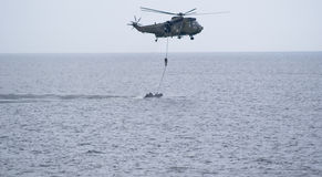 Military training mission. Royal Marine Commando, armed with weapons is transferred between a helicopter and a boat as part of a demonstration at the Sunderland Royalty Free Stock Photos