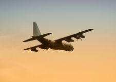 Military transport aircraft. Military cargo transport aircraft in flight at dawn stock image