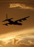 Military transport airplane. Military freight transport plane in flight at dawn Stock Image