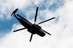 Military transport helicopter on the cloudy sky. Stock Image