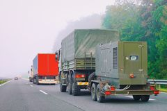 Military truck carrying trailer in road in Slovenia. Military truck carrying trailer in the asphalt road in Slovenia stock photography
