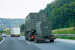 Military truck carrying trailer in road of Slovenia. Military truck carrying trailer in the asphalt road of Slovenia royalty free stock photos
