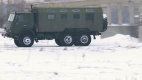 Military truck crosses a snowy field. Military heavy truck -Kamaz- with booth quickly rides on snowy field stock footage