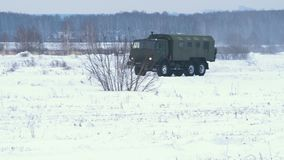 Military truck crosses a snowy field stock video