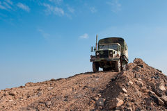 Military Truck on a Dirt Hill. Surplus military truck displayed on a large dirt hill stock photo