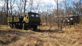 Military truck. Old abandoned green military truck in the middle of the meadow and colorful beehive in the background|autumn|forest Stock Image