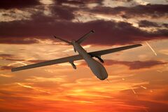 Free Military UAV Airplane Flies Against Backdrop Of Beautiful Sunset Sky Is Orange With Clouds And Condensation Traces Stock Images - 170205834