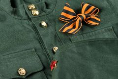 Military uniform with a bow of orange-black St. George ribbon stock photo