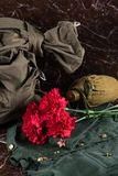 Military uniform, flask, bag and red flowers lie on the background of a brown marble slab Stock Photography