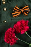 Military uniform and two red flowers with orange ribbon, closeup stock photo