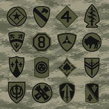 Military unit patch insignia set on green camouflage. Various military patches and insignias suitable more multiple uses Royalty Free Stock Photo