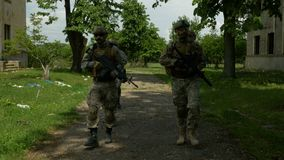 Military unit walking and patrolling near an abandoned building on a sunny day looking for the enemy stock footage