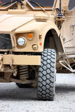 A military vehicle. A military armored tactical vehicle closeup, tire and headlights stock image