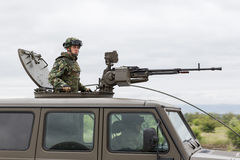 Military vehicle with heavy machine gun and soldier Stock Photos