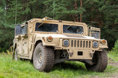 Military vehicle stands on green terrain Royalty Free Stock Photo