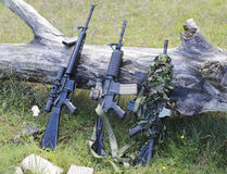 Military weapons for airsoft in a clearing. Near a wood Royalty Free Stock Photos