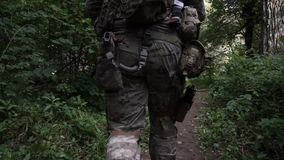 Military weapons are in the woods. The soldier is moving in the forest. Armed man. An armed soldier walks through the woods. Adult military uniforms in the army stock footage