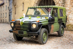 Military wedding vehicle. A photo of a military 4x4 vehicle decorated for weddings with flowers and white ribbon royalty free stock image