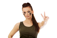 Military woman gesturing peace with fingers Royalty Free Stock Photography