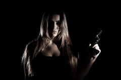 Military woman with a gun. Over black background Royalty Free Stock Image