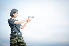 Military woman shooting a gun Stock Image