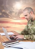 Military working on his laptop against american flag Stock Photos
