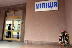 Militian arbitrariness. Mourning wreath near a police station signboard. In glass doors reflection of militiamen and the Ukrainian flag Royalty Free Stock Image