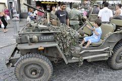 Militär jeep för tappning som är drivande vid ett barn. Royaltyfria Bilder