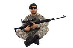 Militär som ner sitter med en prickskyttriffle Arkivfoto
