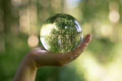 Miljö- begrepp för värld Crystal jordklot i mänsklig hand på härlig gräsplan- och blåttbokeh Arkivbilder