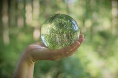 Miljö- begrepp för värld Crystal jordklot i mänsklig hand på härlig gräsplan- och blåttbokeh Royaltyfria Foton