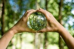 Miljö- begrepp för värld Crystal jordklot i mänsklig hand på härlig gräsplan- och blåttbokeh Royaltyfria Bilder