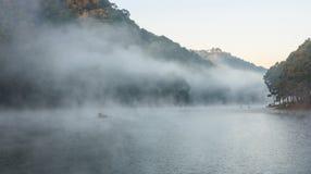 Miljö- vänlig utomhus- aktivitet som svävar bambu som Rafting i morgonen i den fridfulla sjön med solljus och mistvatten Arkivfoton