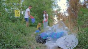 Miljöbelastning, kvinnan och mannen med ungeflickan samlar kull in i avfallpåse i unfocused stundlokalvårdnatur stock video