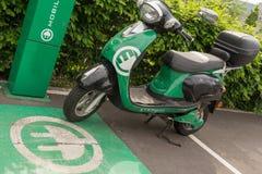 Miljövänlig elektrisk sparkcykel på päfyllningsstationen Arkivbild