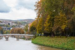 Miljacka河的堤防在秋天的萨拉热窝 达成协议波斯尼亚夹子色的greyed黑塞哥维那包括专业的区区映射路径替补被遮蔽的状态周围的领土对都市植被 免版税库存图片