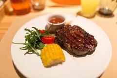 Miljonärfrukost: saftig nötköttbiff med grönsakgarnering på en vit platta Selektivt fokusera Arkivfoto