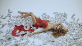 Miljon?rkvinna som ligger i pengar Valuta kvinnor som segrar Sexig kvinna som ligger i dollarr?kningar Flicka i elegant r?d kl?nn stock video