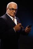 Miljonair rokende sigaar die mobilofoon met behulp van Stock Foto's