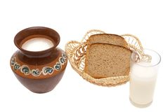 Milk. Milk in a jug and a glass, black bread in a wattled plate on a white background Royalty Free Stock Photo