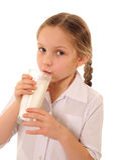 Milk. Cute little girl drinking milk Stock Image