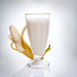 Milk banana smoothie. Still life of a glass filled with milk banana smoothie with fresh banana on background Stock Photo