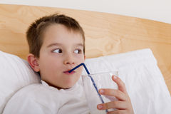 Milk in the Bed. Seven years old drinking his milk in the bed Royalty Free Stock Photography