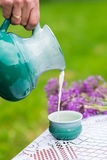 Milk being poured into cup. Milk being poured into turquoise cup from ceramic pot Stock Photography