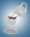 Milk being poured into small cup of coffee. 3d. Milk being poured into small cup of coffee. Blue background. 3d rendering Stock Image