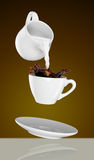 Milk being poured into small cup of coffee. 3d Royalty Free Stock Photos