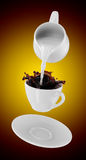 Milk being poured into small cup of coffee. 3d Stock Images