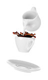 Milk being poured into small cup of coffee. Isolated white background Stock Photo