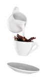 Milk being poured into small cup of coffee.  white background Stock Image
